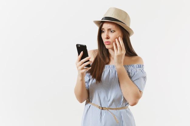 Überrascht verärgert junge frau gekleidet blaues kleid, hut hat einige probleme, hört gefälschte nachrichten oder unerwartete gerüchte im handy isoliert auf weißem hintergrund. menschen, aufrichtige emotionen, lifestyle-konzept.
