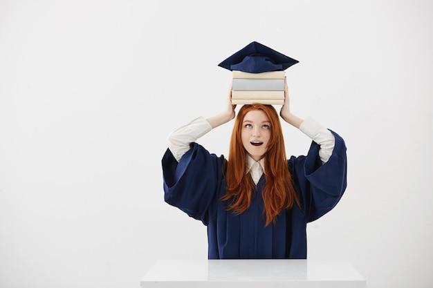 Überraschte absolventin der frau, die bücher auf kopf unter kappe hält.