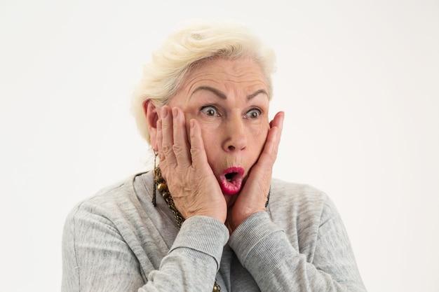 Überraschte ältere dame isolierte frau mit händen im gesicht sehen das unglaubliche