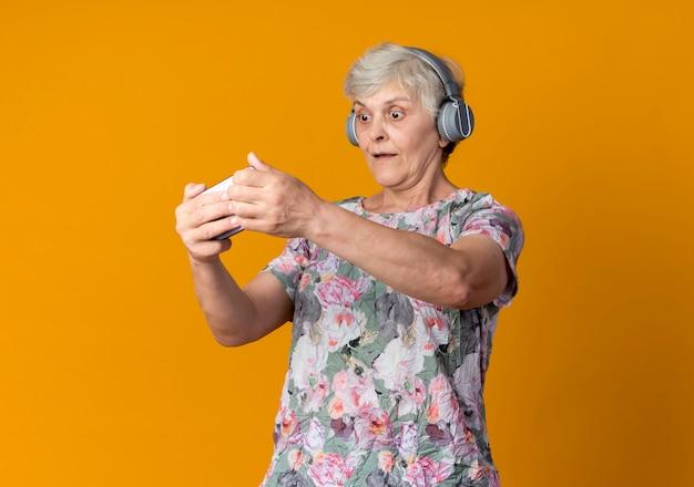 Überraschte ältere frau auf kopfhörern, die telefon lokalisiert auf orange wand halten und betrachten