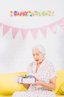 Überraschte ältere frau, die geburtstagsgeschenk betrachtet