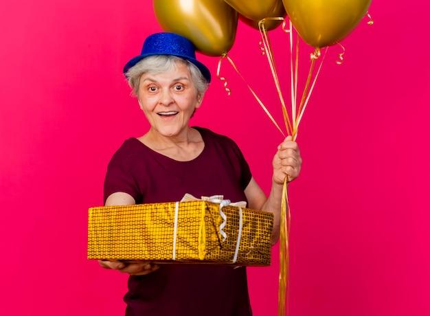 Überraschte ältere frau, die partyhut hält, der heliumballons und geschenkbox auf rosa hält