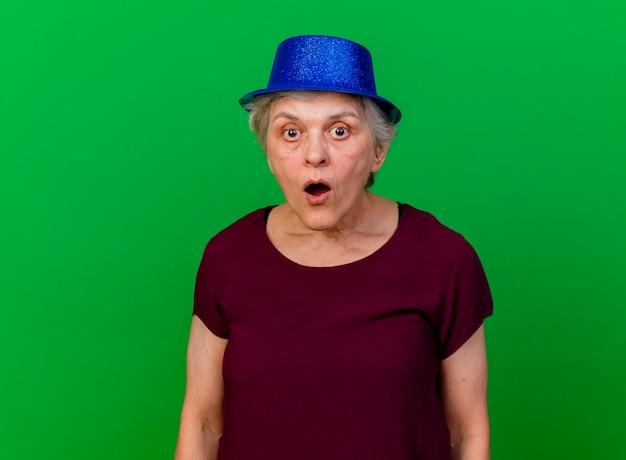 Überraschte ältere frau, die partyhut trägt, betrachtet kamera auf grün