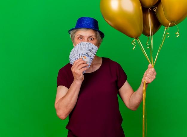 Überraschte ältere frau, die partyhut trägt, hält geld und heliumballons auf grün