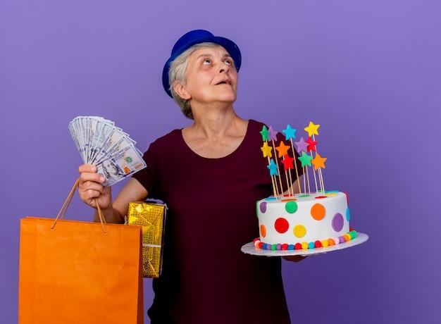Überraschte ältere frau, die partyhut trägt, hält geldgeschenkboxpapier-einkaufstasche und geburtstagstorte, die seite lokalisiert auf lila wand mit kopienraum betrachten