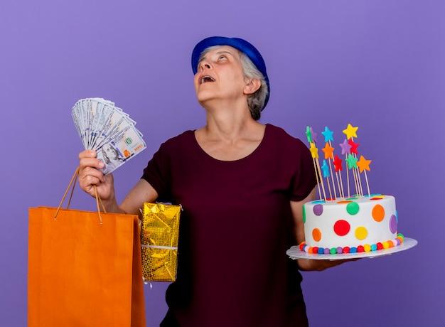 Überraschte ältere frau, die partyhut trägt, hält geldgeschenkboxpapier-einkaufstasche und geburtstagstorte lokalisiert auf lila wand mit kopienraum