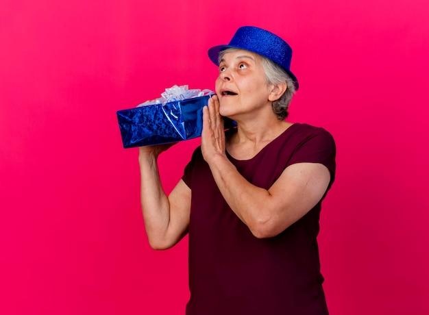 Überraschte ältere frau, die partyhut trägt, hält geschenkbox, die auf rosa schaut