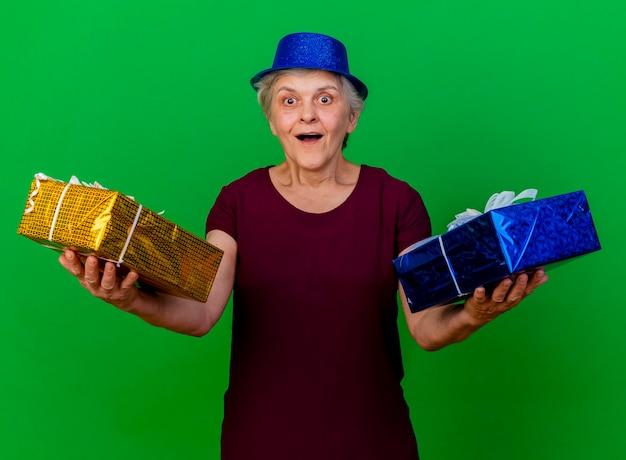 Überraschte ältere frau, die partyhut trägt, hält geschenkboxen auf grün