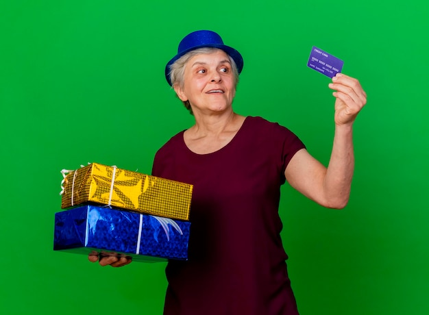 Überraschte ältere frau, die partyhut trägt, hält geschenkboxen und schaut auf kreditkarte auf grün
