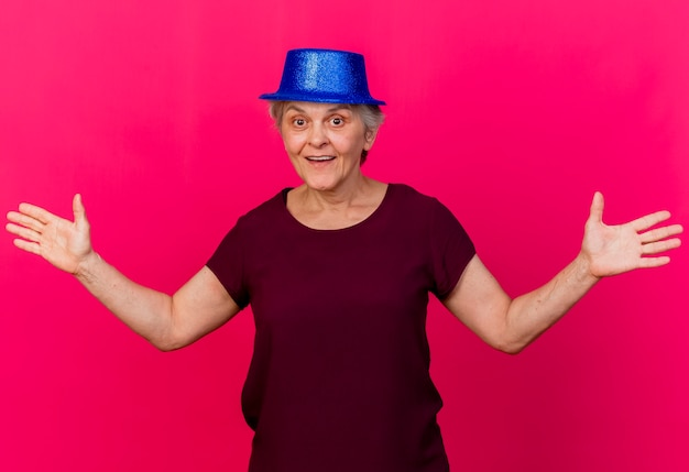 Überraschte ältere frau, die partyhut trägt, hält händchenhalten offen und betrachtet front lokalisiert auf rosa wand