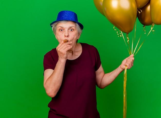 Überraschte ältere frau, die partyhut trägt, hält heliumballons, die pfeife auf grün blasen