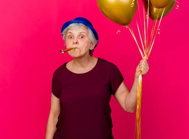 Überraschte ältere frau, die partyhut trägt, hält heliumballons, die pfeife auf rosa blasen
