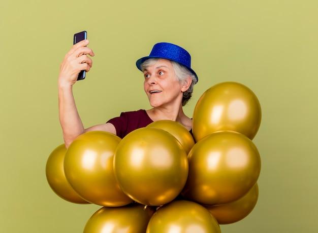 Überraschte ältere frau, die partyhut trägt, hält heliumballons und betrachtet telefon lokalisiert auf olivgrüner wand mit kopienraum