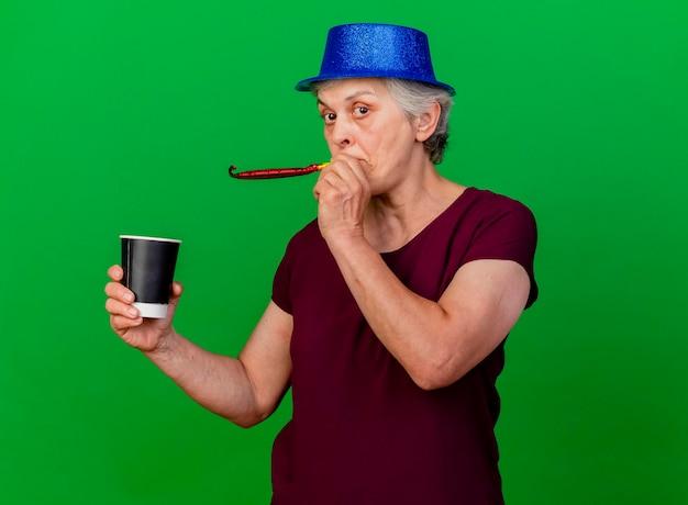 Überraschte ältere frau, die partyhut trägt, hält tasse und pfeift auf grün