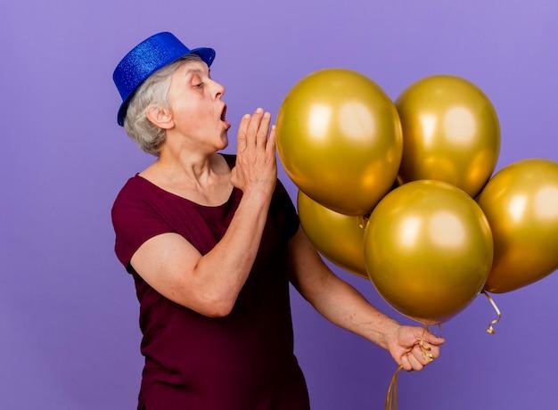 Überraschte ältere frau, die partyhut trägt, hält und betrachtet heliumballons auf purpur