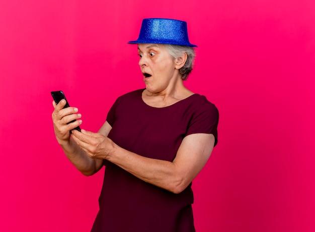Überraschte ältere frau, die partyhut trägt, hält und schaut auf telefon auf rosa