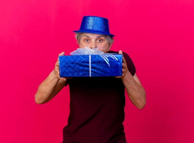 Überraschte ältere frau, die partyhut trägt, hält und schaut kamera über geschenkbox auf rosa