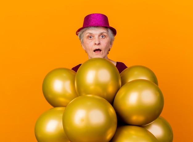 Überraschte ältere frau, die partyhut trägt, steht mit heliumballons auf orange