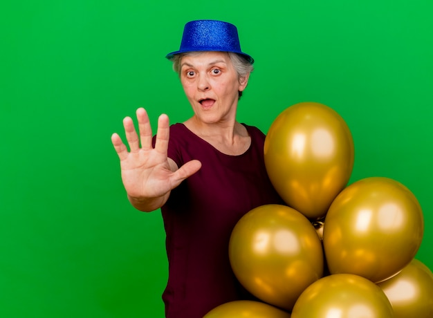Überraschte ältere frau, die partyhut trägt, steht mit heliumballons, die hand auf grün ausstrecken Kostenlose Fotos