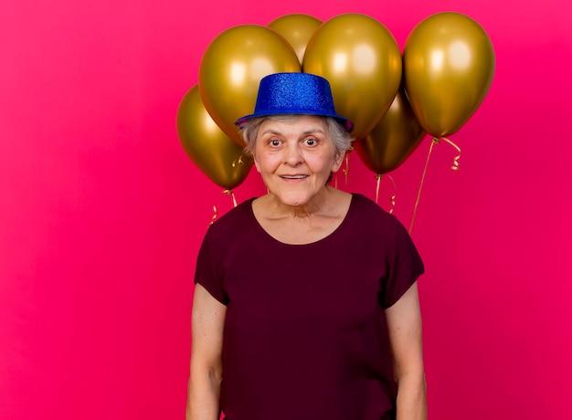 Überraschte ältere frau, die partyhut trägt, steht vor heliumballons, die kamera auf rosa betrachten