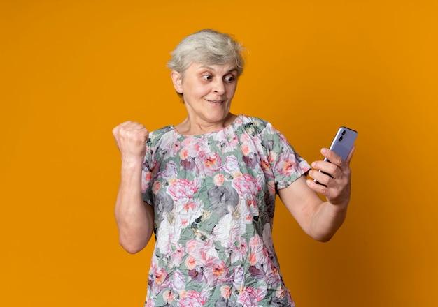 Überraschte ältere frau erhebt faust, die telefon hält und betrachtet, das auf orange wand lokalisiert wird