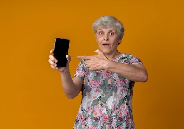 Überraschte ältere frau hält und zeigt auf telefon lokalisiert auf orange wand