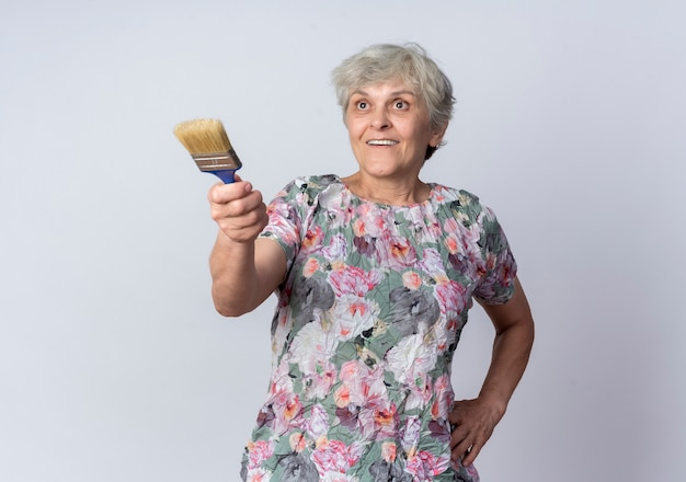 Überraschte ältere frau hält und zeigt nach vorne mit pinsel isoliert auf weißer wand