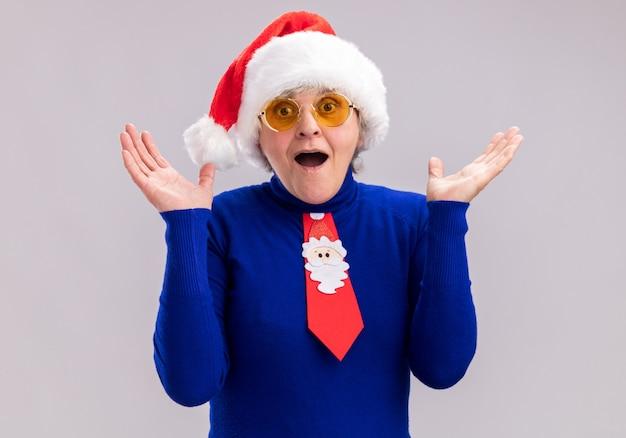 Überraschte ältere frau in sonnenbrille mit weihnachtsmütze und weihnachtskrawatte