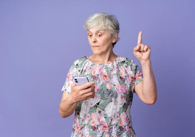 Überraschte ältere frau schaut auf telefon und zeigt isoliert auf lila wand