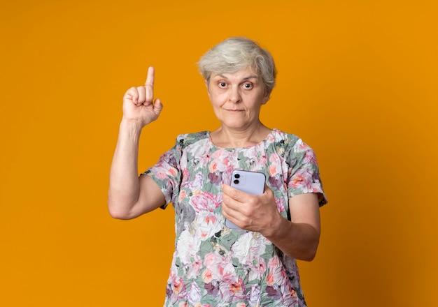 Überraschte ältere frau zeigt auf, telefon lokalisiert auf orange wand zu halten