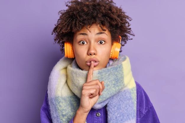 Überraschte afroamerikanerin drückt zeigefinger auf die lippen macht stille geste sagt geheimnis trägt warmen schal um den hals hört musik über drahtlose kopfhörer.