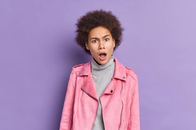 Überraschte afroamerikanerin mit lockigem buschigem haar sieht empört aus, hat den mund weit geöffnet