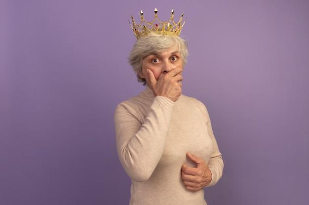 Überraschte alte frau mit cremigem rollkragenpullover und krone, die hand auf mund und bauch legt