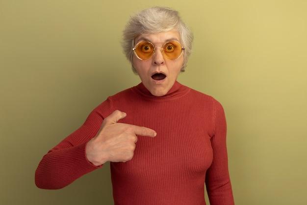 Überraschte alte frau mit rotem rollkragenpullover und sonnenbrille, die auf den raum vor ihr zeigt, isoliert auf olivgrüner wand mit kopierraum