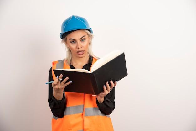 Überraschte arbeiterin, die notizen auf weißem hintergrund liest. hochwertiges foto