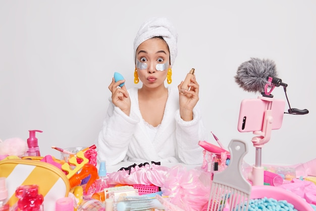 Überraschte asiatische dame mit gefalteten lippen wirbt für neue stiftung empfiehlt kosmetisches produkt hat online-übersetzung auf der website verwendet kostenlose internetverbindung verwendet schönheitsflecken unter den augen.