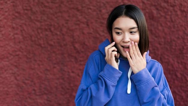 Überraschte asiatische frau, die am telefon spricht