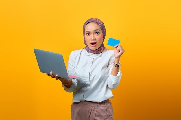 Überraschte asiatische frau, die laptop hält und leere karte auf gelbem hintergrund zeigt