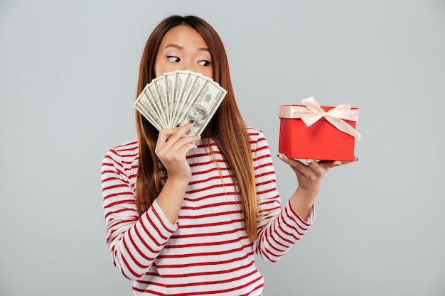 Überraschte asiatische frau im pullover, der sich hinter einem geld versteckt und geschenk über grauem hintergrund betrachtet