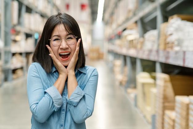 Überraschte asiatische kundin, die kamera schaut und mit rabatt und verkauf glücklich sich fühlt. asiatische unternehmerfreude und -spaß mit bestandskontrolle im lagerspeicher.
