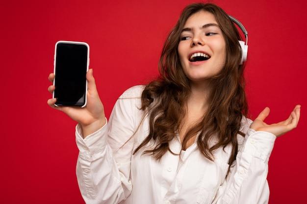 Überraschte attraktive positive junge brünette lockige frau mit weißem hemd isoliert auf rot