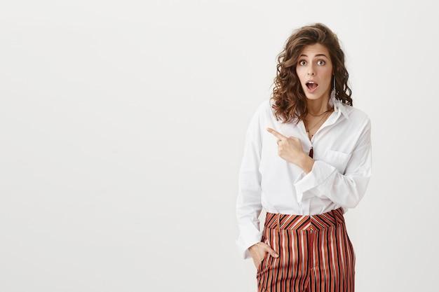 Überraschte attraktive unternehmerin zeigt mit dem finger nach links und lässt den kiefer fallen