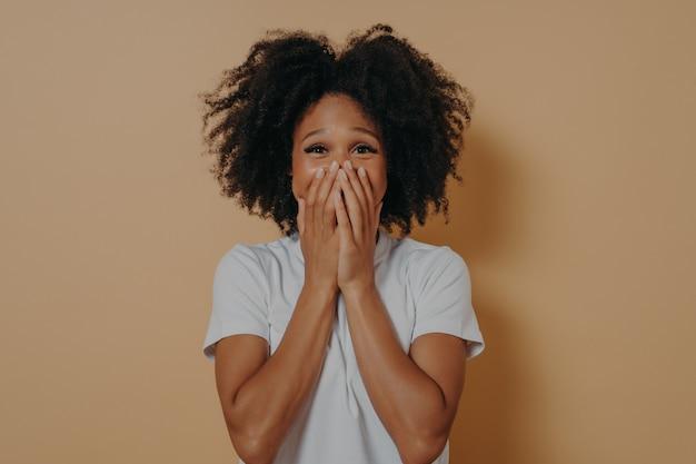 Überraschte aufgeregte dunkelhäutige frau in weißem t-shirt, die ihren mund mit händen bedeckt, einzeln auf pastellbeigem hintergrund mit kopienraum. positive frauengefühle und körpersprachekonzept