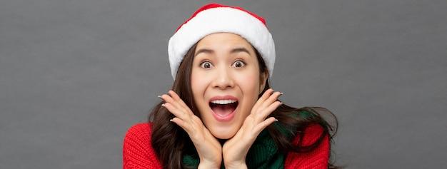 Überraschte aufgeregte schöne asiatin in der roten weihnachtsstrickjacke und -hut