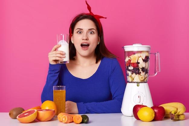 Überraschte beeindruckte brünette frau sitzt mit weit geöffnetem mund am tisch, hält ein glas milchshake in der rechten hand und kocht eine andere fruchtmischung in einem weißen mixer. gesundes lebensstilkonzept.