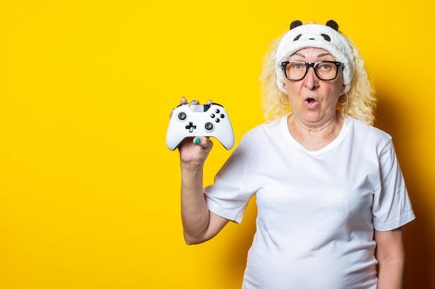 Überraschte blonde alte frau mit joystick in schlafmaske