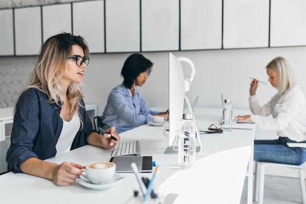 Überraschte blonde frau, die computerbildschirm betrachtet und latte an ihrem arbeitsplatz genießt