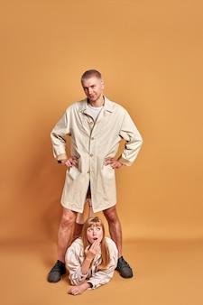 Überraschte blonde frau liegen unter den füßen des isolierten mannes, porträt des jungen mannes im mantel posierend