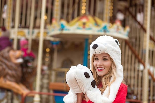 Überraschte blonde frau mit rotem strickpullover und lustigem hut, die im hintergrund des karussells mit lichtern posiert