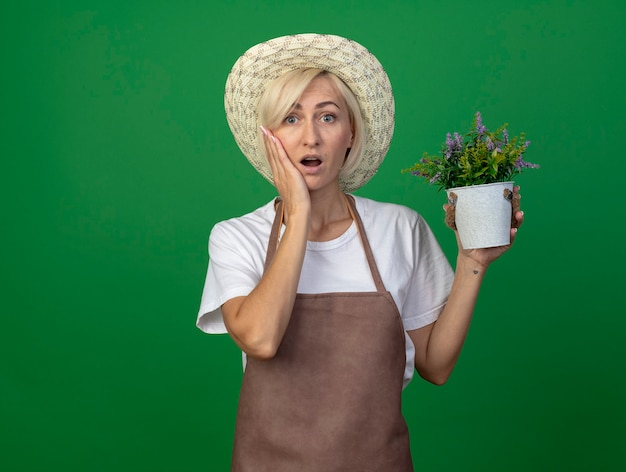 Überraschte blonde gärtnerin mittleren alters in uniform mit hut, der blumentopf hält und die hand auf dem gesicht hält